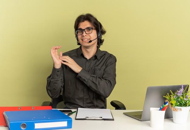 광학 안경에 헤드폰에 젊은 기쁘게 회사원 남자 노트북을 사용하는 사무실 도구와 책상에 앉아 함께 복사 공간이 녹색 배경에 고립 된 손을 보유