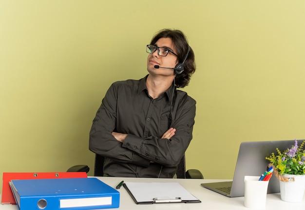 광학 안경에 헤드폰에 젊은 기쁘게 회사원 남자 노트북을 사용하는 사무실 도구와 책상에 앉아 복사 공간이 녹색 배경에 고립 된 교차 팔을 찾습니다
