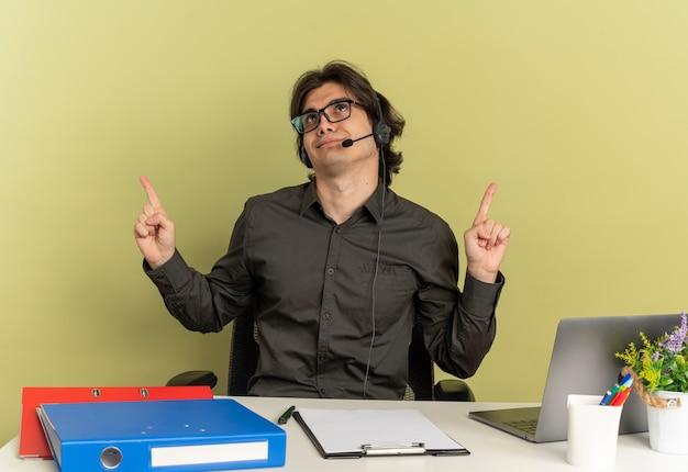 Молодой человек доволен офисным работником в наушниках в оптических очках сидит за столом с офисными инструментами, используя ноутбук, указывает вверх