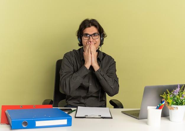 광학 안경에 헤드폰에 젊은 기쁘게 회사원 남자 노트북을 사용하는 사무실 도구와 책상에 앉아 복사 공간이 녹색 배경에 고립 된 카메라를보고 입에 손을 넣습니다