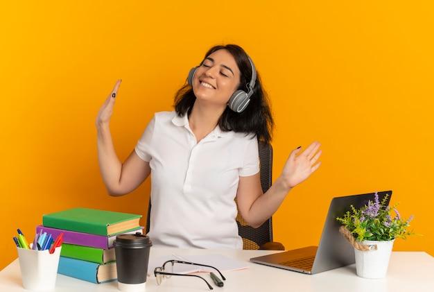 Молодая довольная симпатичная кавказская школьница в наушниках сидит за столом со школьными инструментами с поднятыми руками, изолированными на оранжевом пространстве с копией пространства