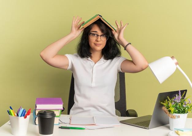 안경을 쓰고 젊은 만족 된 예쁜 백인 여학생 학교 도구로 책상에 앉아 복사 공간이 녹색에 머리 위에 책을 보유