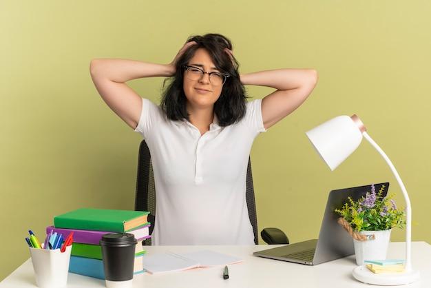 안경을 쓰고 젊은 만족 된 예쁜 백인 여학생 학교 도구로 책상에 앉아 복사 공간이 녹색 공간에 고립 된 머리를 보유