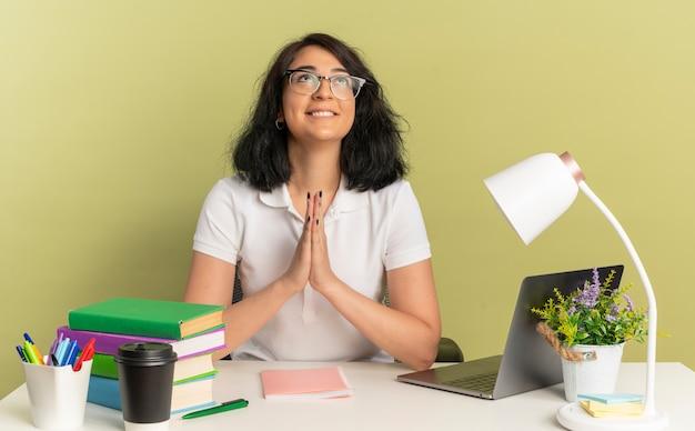 안경을 쓰고 젊은 만족 된 예쁜 백인 여학생 학교 도구와 함께 책상에 앉아 복사 공간이 함께 녹색 공간에 고립 손을 잡고 조회