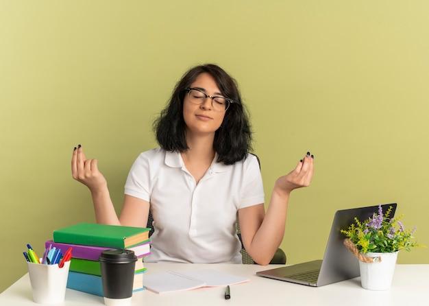 안경을 쓰고 젊은 만족 예쁜 백인 여학생 학교 도구와 책상에 앉아 복사 공간이 녹색 공간에 고립 제기 손으로 명상 척