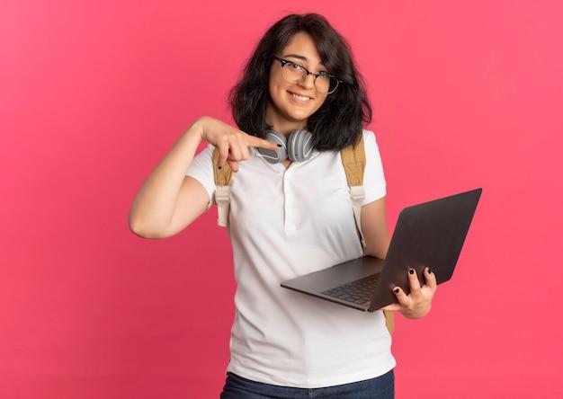 Молодая довольная симпатичная кавказская школьница с наушниками на шее в очках и задней сумке держит и указывает на ноутбук на розовом с копией пространства