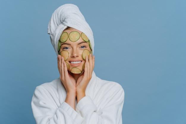 喜ぶ若い女性が顔にきゅうりのスライスを塗り、美容処置を受けて顔のマスクを作る