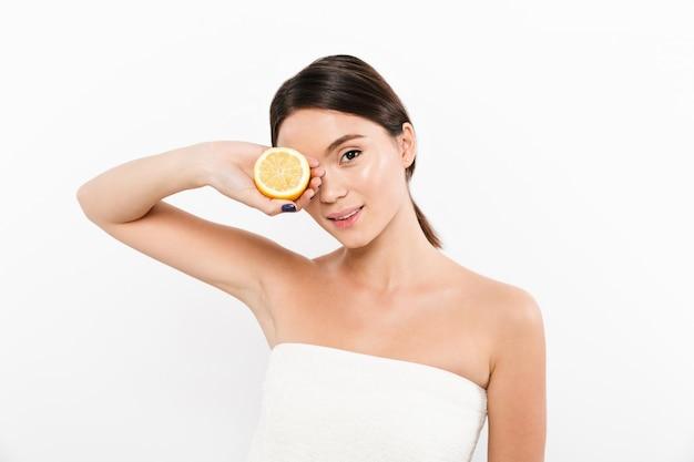 柑橘類を彼女の顔の近くに持って喜んでいる若い女性