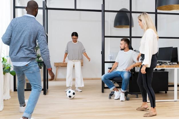 Giovani che giocano con la palla in ufficio