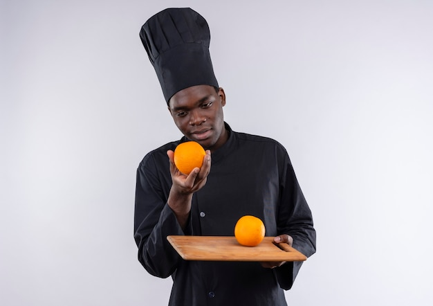 Young plesed afro-american cook in chef uniform holds orange on cutting board and on hand on white  with copy space