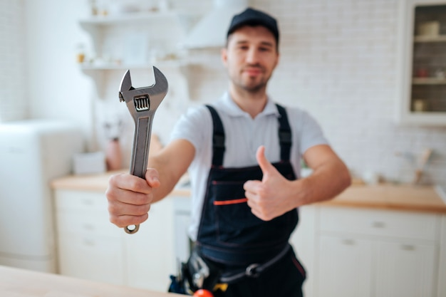 Young plumber hold wrench in hand