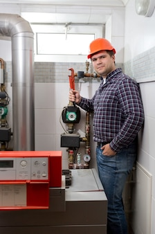 Young plumber installing heating system at boiler room
