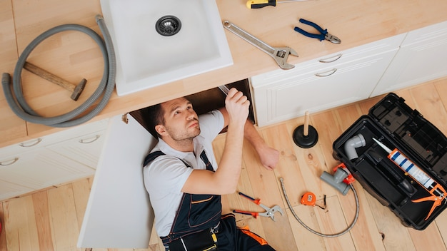 Young plumber look under sink in kitchen