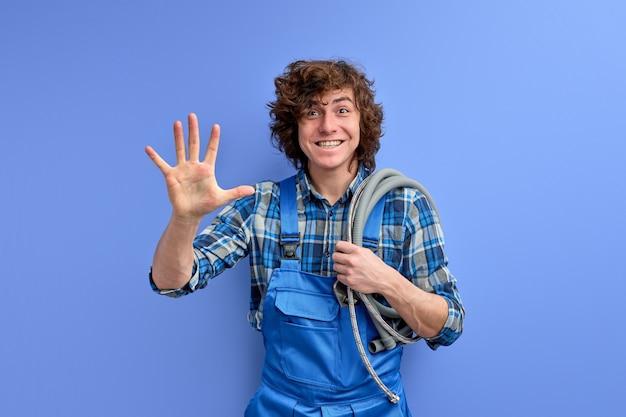 블루 스튜디오 배경 위에 절연 카메라에 손을 흔들며 클라이언트를 환영하는 젊은 배관공 남자.