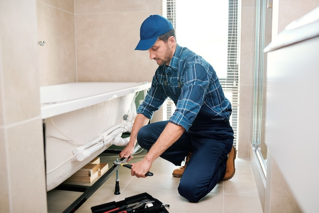 Young plumber or technician in workwear preparing detail for bathtub installation while sitting on squats