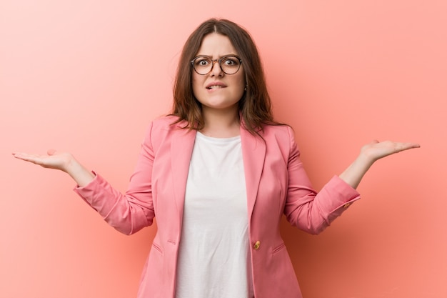 Young plus size business caucasian woman confused and doubtful raising him hands to hold a copy space.