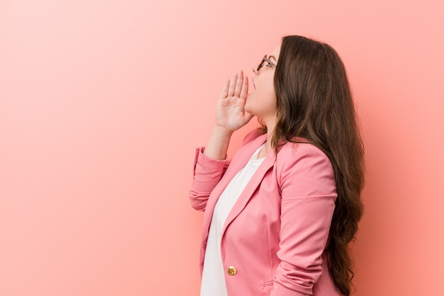 Young plus size business caucasian woman shouting and holding palm near opened mouth.