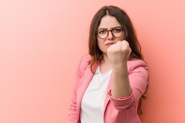Молодые плюс размер бизнес кавказской женщины показаны кулак с агрессивным выражением лица.