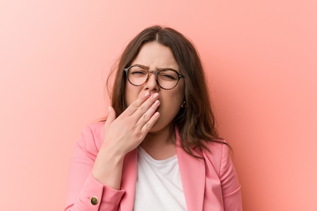 Young plus size business caucasian woman yawning showingtired gesture covering mouth with him hand.