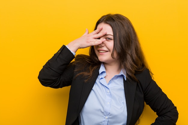 Young plus size caucasian business woman blink at the camera through fingers, embarrassed covering face.
