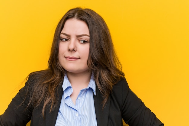 Young plus size caucasian business woman confused, feels doubtful and unsure.