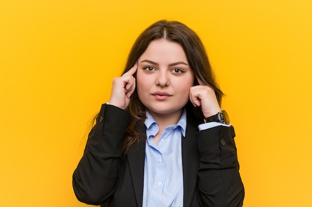 Young plus size caucasian business woman focused on a task, keeping him forefingers pointing head.