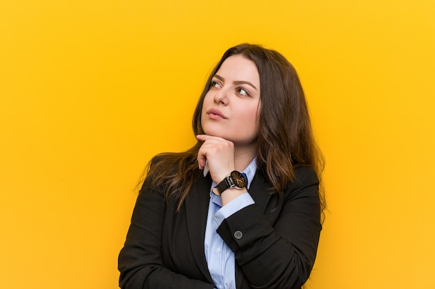 Young plus size caucasian business woman looking sideways with doubtful and skeptical expression.