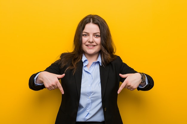 Young plus size caucasian business woman points down with fingers, positive feeling.