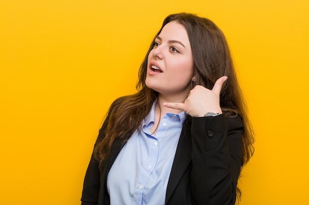 Young plus size caucasian business woman showing a mobile phone call gesture with fingers.