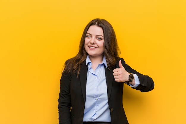 Young plus size caucasian business woman smiling and raising thumb up