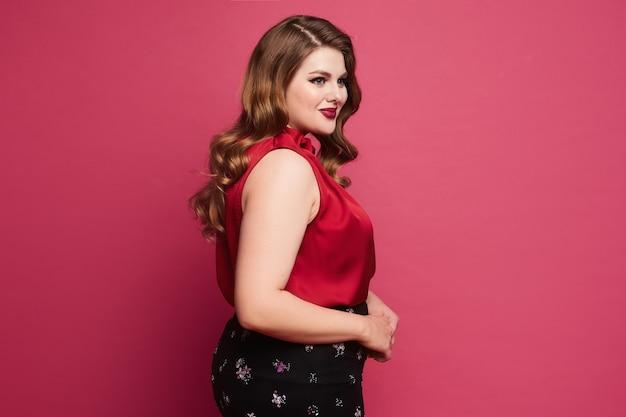 Молодая кавказская модель больших размеров в красной атласной блузке и юбке позирует на розовом фоне ...