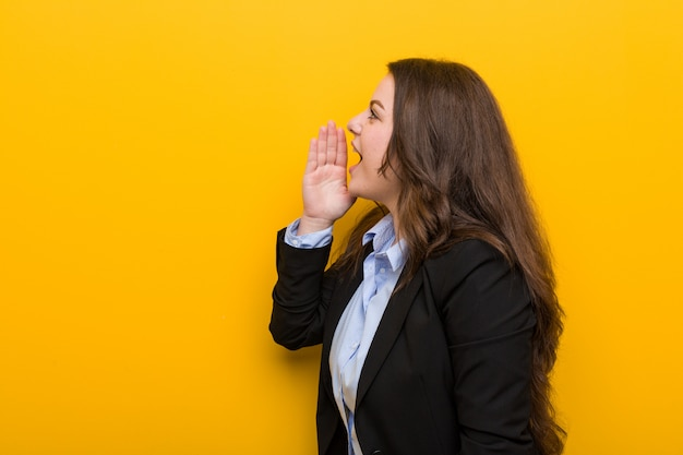 Young plus size caucasian woman shouting and holding palm near opened mouth.