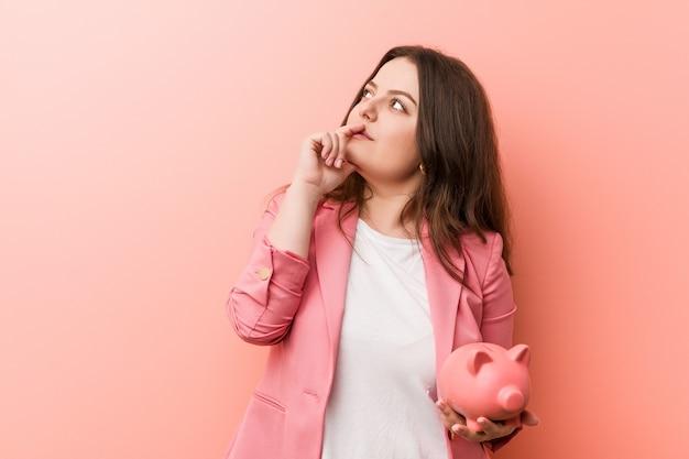 疑わしいと懐疑的な表情で横に見て貯金を保持している若いプラスのサイズの曲線のビジネス女性。