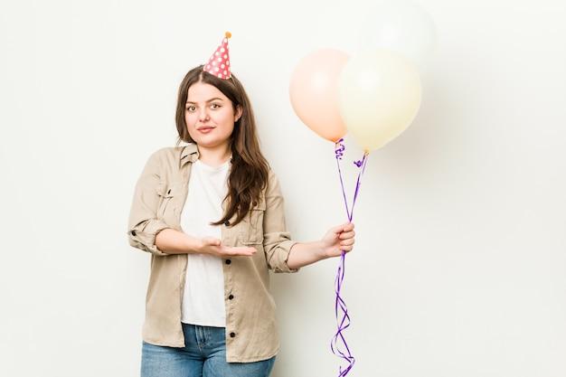 手のひらにコピースペースを示し、腰に別の手を持って誕生日を祝う若いプラスサイズの曲線美の女性。