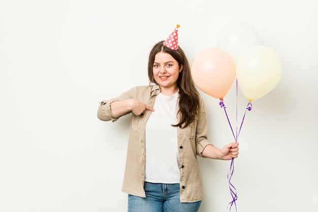 Young plus size curvy woman celebrating a birthday person pointing by hand to a shirt copy space, proud and confident