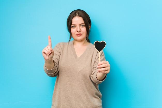 指でナンバーワンを示すハート型を保持している若いプラスサイズの曲線美の女性。