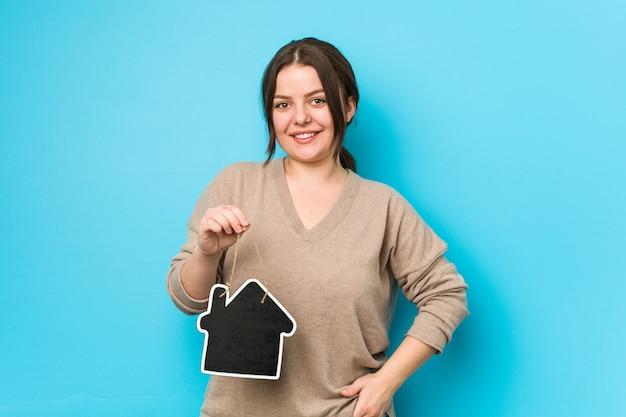 ホームアイコンを保持している幸せな、笑顔で陽気な若いプラスサイズの曲線の女性。