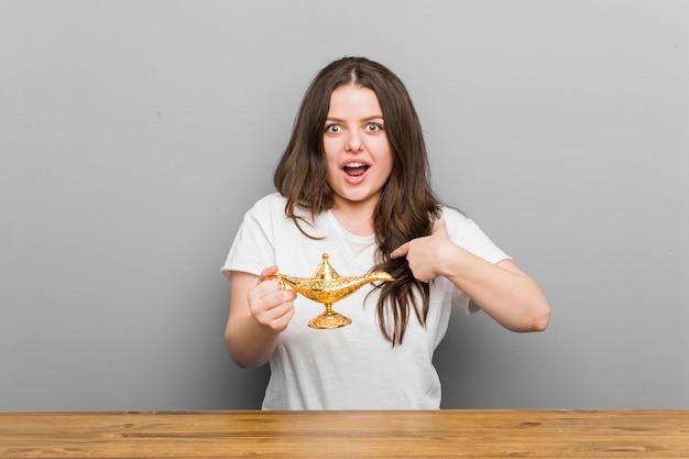 魔法のランプを持った若いプラスサイズの曲線美の女性は、自分自身を指して驚いて、大きく笑っていました。