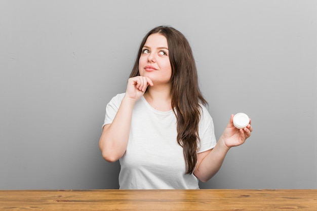 疑わしいと懐疑的な表情で横向きに保湿剤を保持している若いプラスのサイズの曲線の女性。
