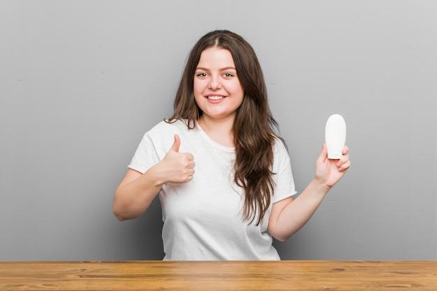 若いプラスのサイズの曲線美の女性の笑顔と親指を上げる保湿剤を保持