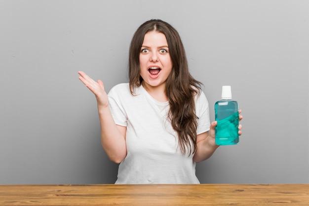 Молодая фигуристая женщина большого размера с жидкостью для полоскания рта празднует победу или успех