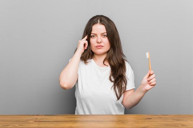 Молодая фигуристая женщина большого размера держит зубную щетку, указывая пальцем в висок, думает, сосредоточена на задаче.