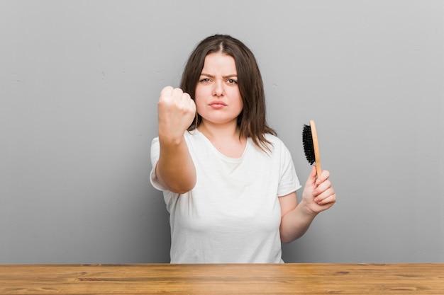 Молодой плюс размер соблазнительная женщина, держащая расческу, показывая кулак, агрессивное выражение лица.