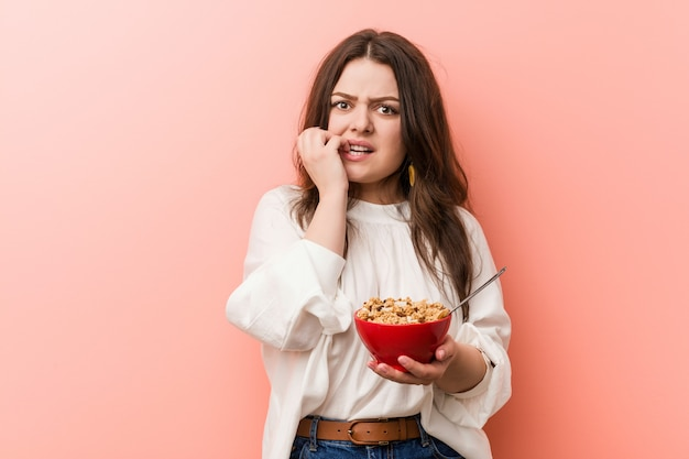 Young plus size curvy woman holding a cereals bowl biting fingernails, nervous and very anxious.