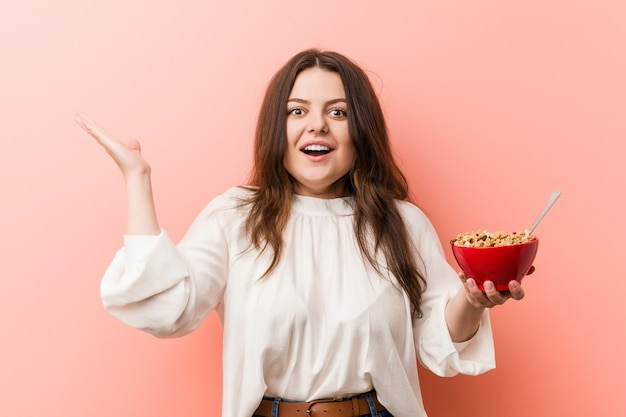 Young plus size curvy woman holding a cereals bowl celebrating a victory or success