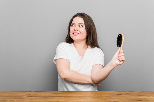 Young plus size curvy woman holding an hairbrush smiling confident with crossed arms.
