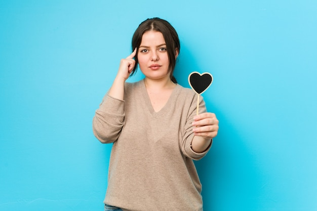 Young plus size curvy woman holding a heart shape pointing his temple with finger, thinking, focused on a task.