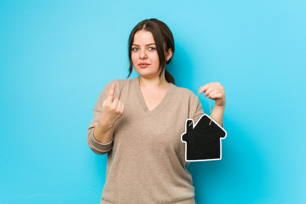 Young plus size curvy woman holding a home icon pointing with finger at you as if inviting come closer.