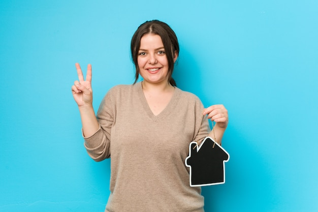Young plus size curvy woman holding a home icon showing number two with fingers.