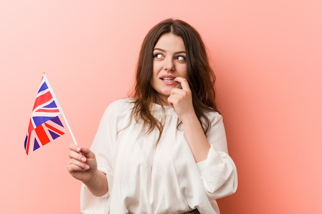 Young plus size curvy woman holding a united kingdom flag relaxed thinking about something looking at a copy space.